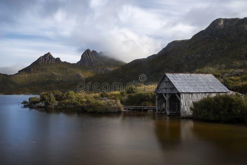 Barco vertido en el lago con la montaña fotografía de archivo