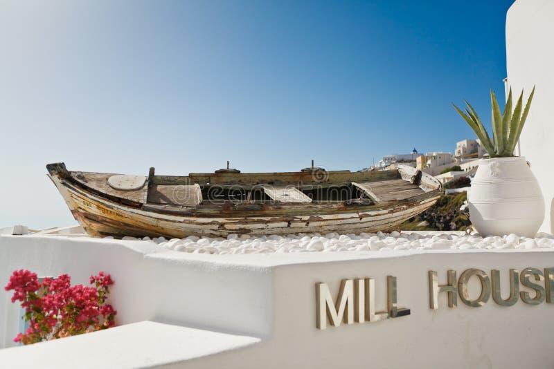 Barco viejo en una terraza con la opinión sobre la arquitectura blanca de Santorini, Grecia imagen de archivo