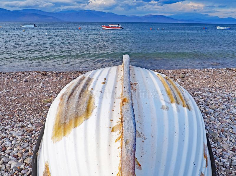 Barco vuelto hacia arriba en la playa y el golfo del Corinthian, Grecia de Nikolaiika fotos de archivo