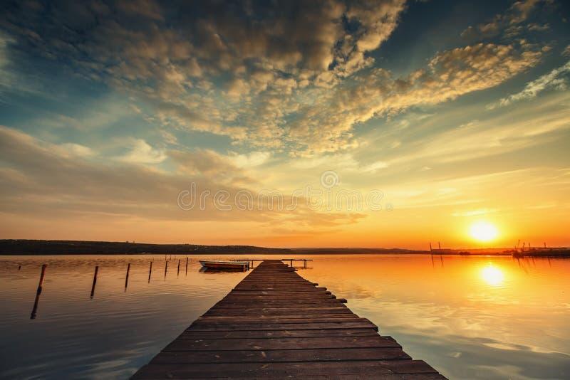 Barco y embarcadero en el lago con una reflexión en el agua en la puesta del sol foto de archivo libre de regalías