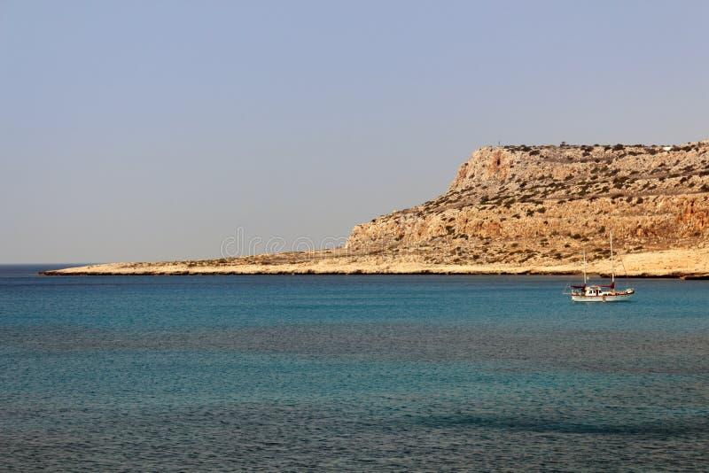 Barco y península en el cabo Greco Chipre imagenes de archivo