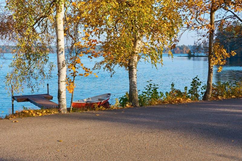 Barco y pont rojos en la costa del lago con agua azul en una carretera del fondo y de asfalto en un primero plano foto de archivo