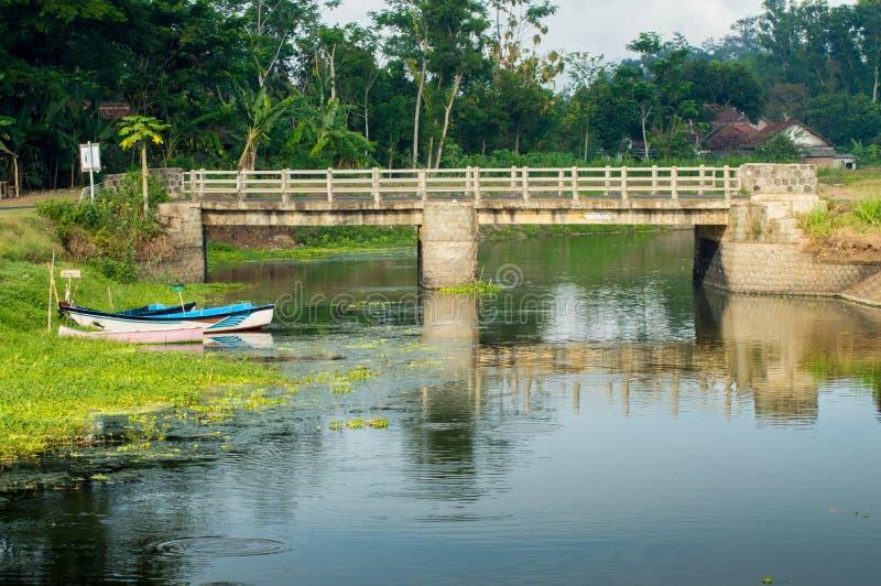 Barco y puente en un río tranquilo imagen de archivo