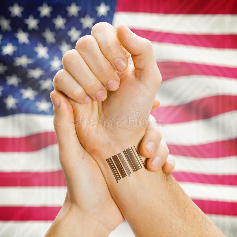 Barcode ID number on wrist and national flag on background series - United States - USA. Barcode ID number on wrist of a human and national flag on background royalty free stock photo