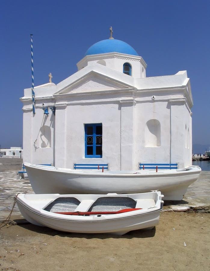 Barcos al lado de la iglesia de la playa, Mykonos, Grecia imagenes de archivo