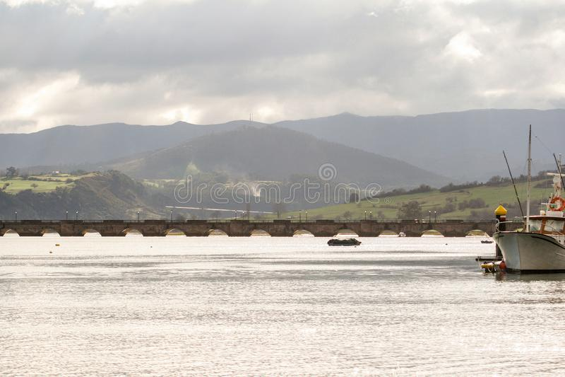 Barcos amarrados en puerto con el puente de San Vicende de la barquera, de Cantabria, de monta?as y del cielo nublado en el fondo imagenes de archivo