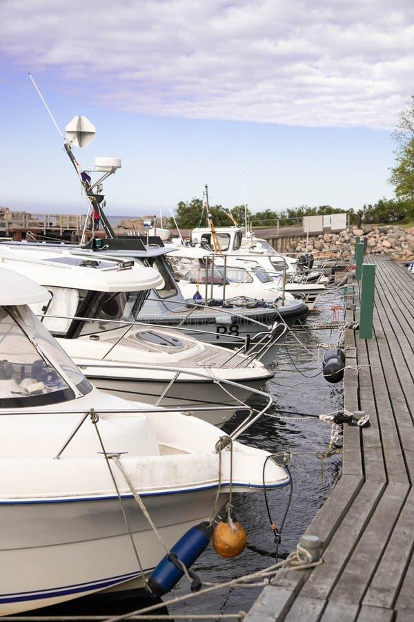 Barcos atracados Barcos amarrados Barcos que se colocan en fila en un embarcadero de madera Barcos atracados fotos de archivo libres de regalías