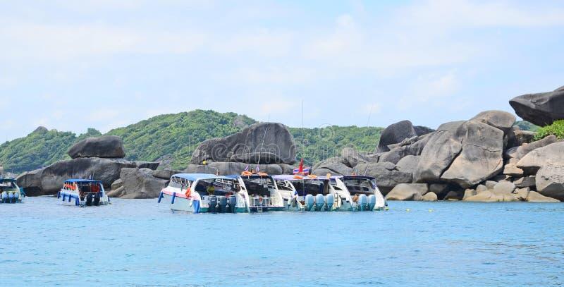 Barcos atracados de la velocidad en el mar azul al lado de la isla de piedra fotografía de archivo libre de regalías