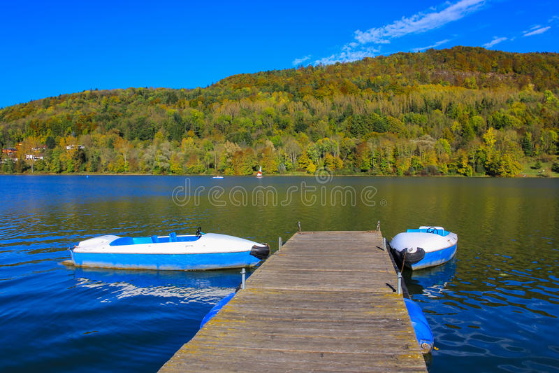 Barcos azuis no molhe para amarrar - lago colorido do outono fotos de stock royalty free