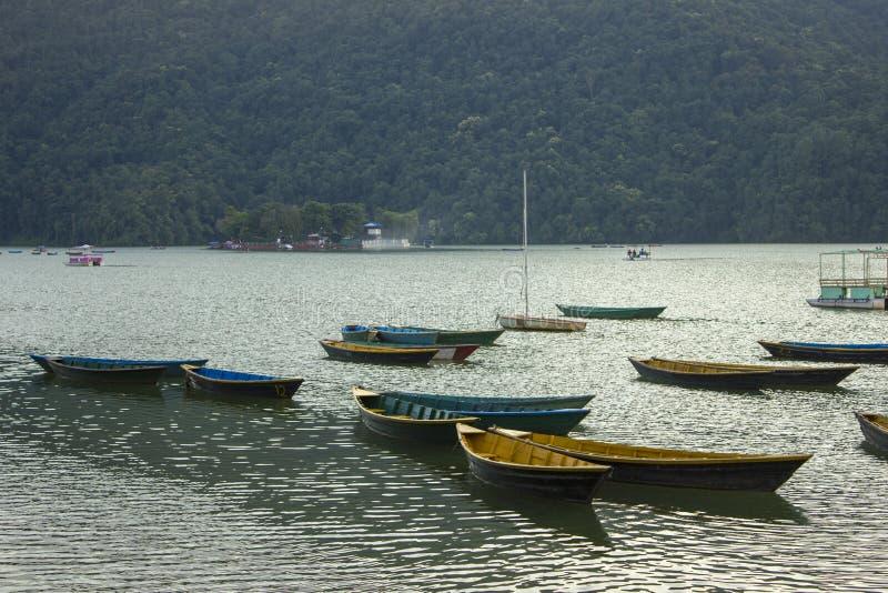 Barcos coloreados brillantes vacíos viejos de madera en el lago Phewa en el fondo de una montaña con un bosque verde fotografía de archivo