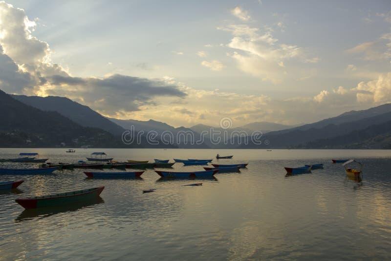 Barcos coloreados vacíos viejos de madera en el lago Phewa en el fondo de un valle de la tarde de la montaña en la niebla fotografía de archivo