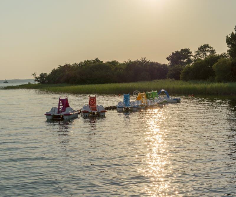 Barcos coloridos do pedal com corrediças de água na superfície da água do lago imagem de stock