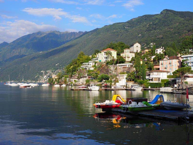 Barcos coloridos en asilo en ciudad del viaje de Ascona con la opinión sobre el lago Maggiore en Suiza foto de archivo libre de regalías