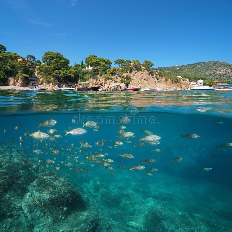 Barcos da Espanha perto da costa rochosa e peixes subaquáticos foto de stock