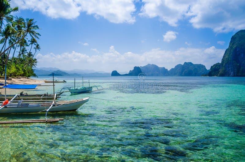 Barcos de Banca na água clara no Sandy Beach no EL Nido, Filipinas fotos de stock royalty free