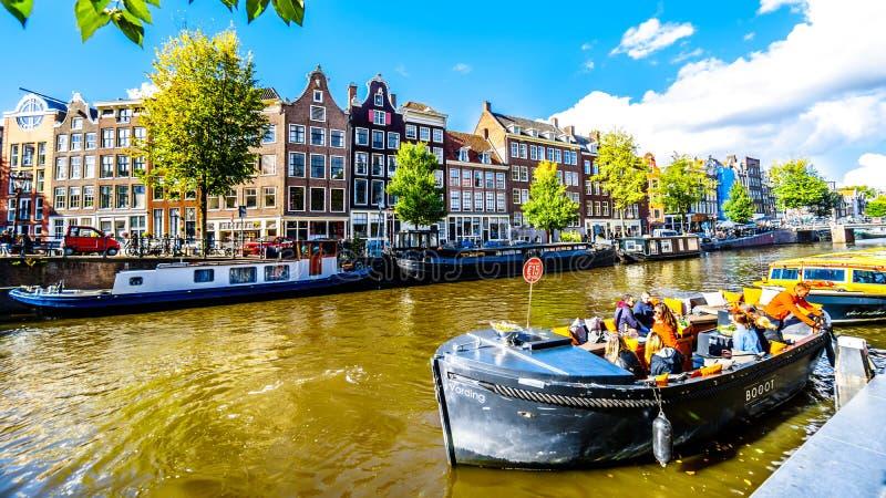 Barcos de canal turísticos que amarran en Anne Frank House en el príncipe Canal de Prinsengracht en la vecindad de Jordaan en Ams foto de archivo