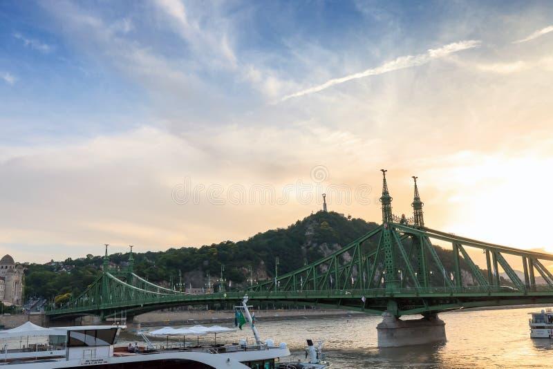 Barcos de cruceros en el río Danubio y la colina de Gellert en la puesta del sol imagenes de archivo