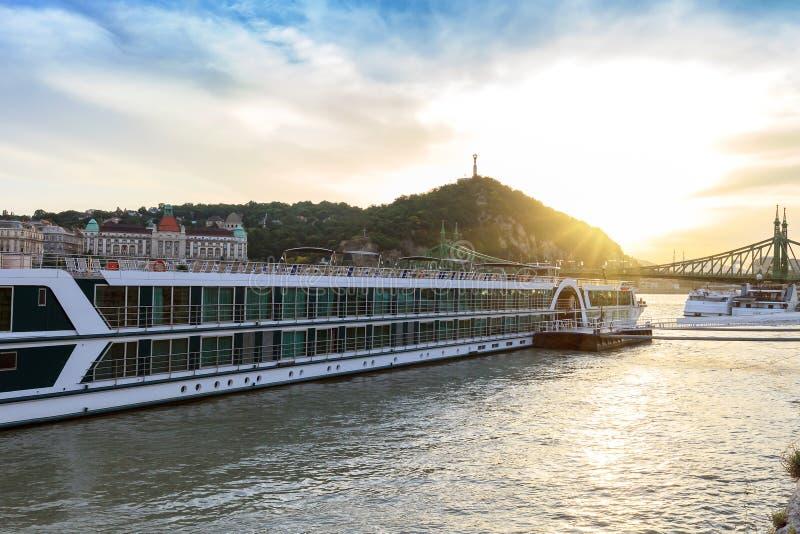 Barcos de cruceros en el río y la colina de Gellert en la puesta del sol en Budapest, Hungría foto de archivo