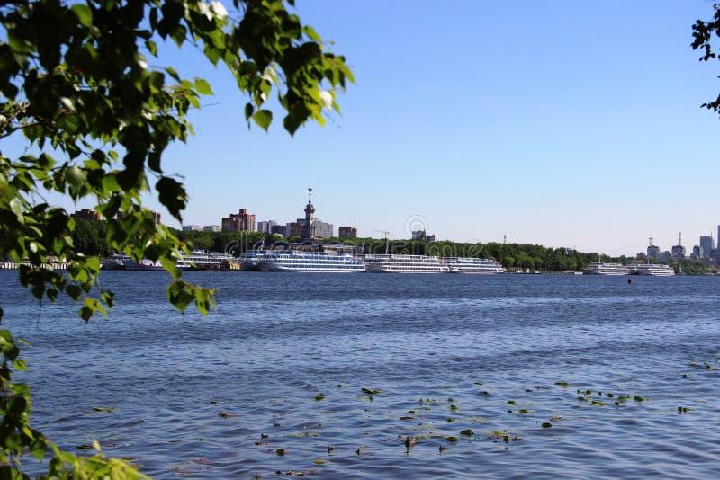 Barcos de cruceros grandes y pequeñas naves en el río portuario de Moscú, la visión desde el banco opuesto enmarcado por las rama imagen de archivo