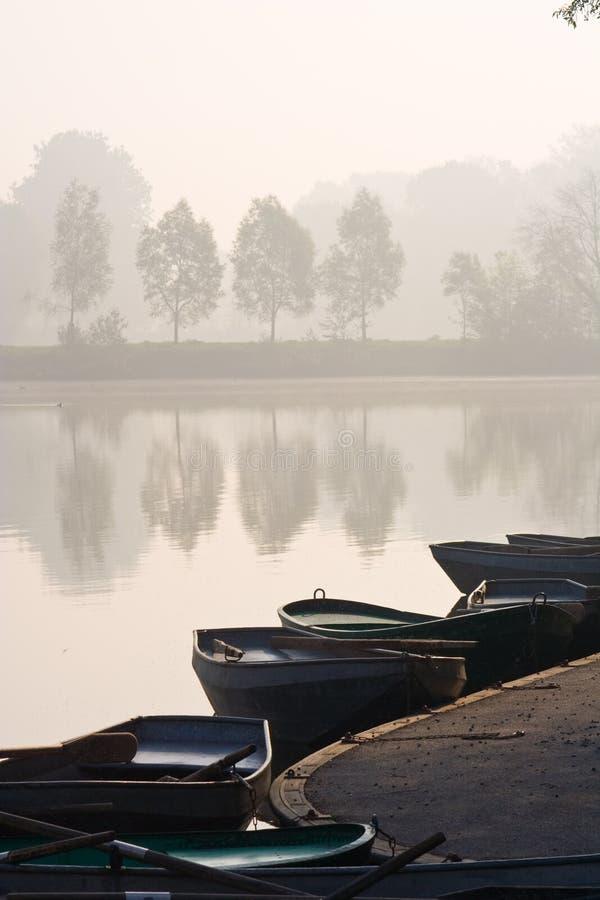 Barcos de enfileiramento na lagoa enevoada fotos de stock royalty free