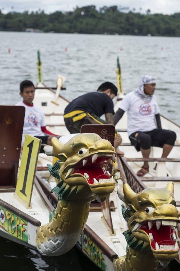 Barcos de fila nativos de los deportes parqueados en a orillas del lago durante Dragon Cup Competition fotografía de archivo libre de regalías