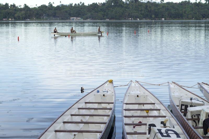 Barcos de fila nativos de los deportes parqueados en a orillas del lago durante Dragon Cup Competition imágenes de archivo libres de regalías