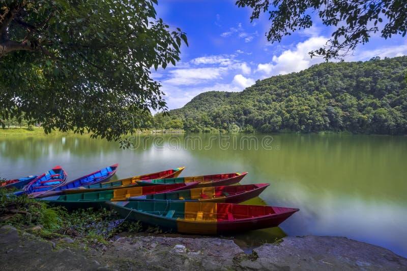 Barcos de fileira bonitos no lago Phewa e no céu azul no fundo fotos de stock