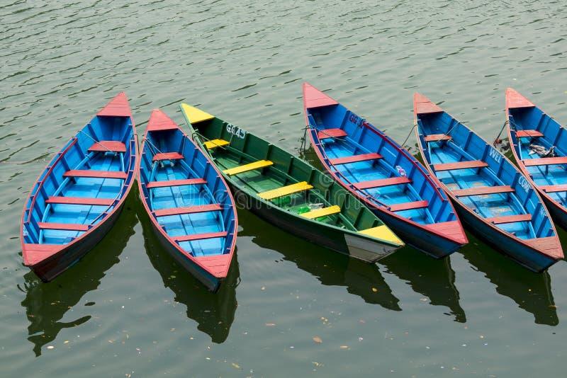 Barcos de fileira coloridos entrados no lago Phewa em Pokhara foto de stock royalty free