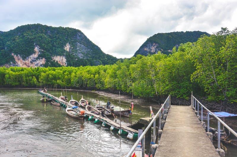 Barcos de la cola larga del pescador que parquean en el embarcadero en playa del bosque del mangle con el fondo de la montaña y d foto de archivo libre de regalías