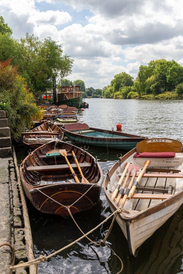 Barcos de madeira para o aluguer amarrados no rio Tamisa foto de stock