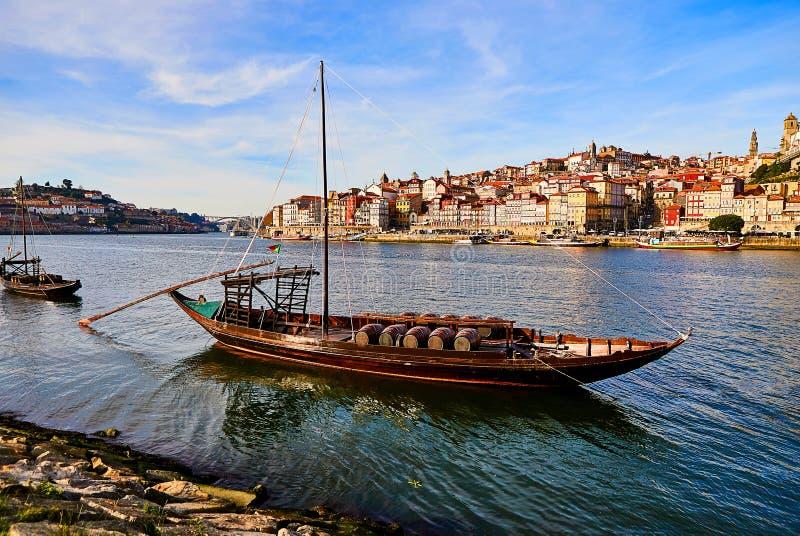 Barcos de madeira portugueses t?picos, chamados ?rabelos dos barcos ?que transportam tambores de vinho no rio Douro com vista na  imagem de stock