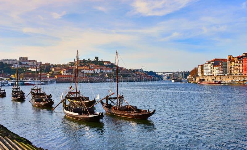 Barcos de madeira portugueses t?picos, chamados ?rabelos dos barcos ?que transportam tambores de vinho no rio Douro com vista na  fotografia de stock