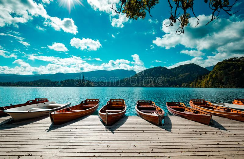 Barcos de madeira tradicionais Pletna no backgorund da igreja na ilha no lago sangrado, Eslovênia europa fotografia de stock