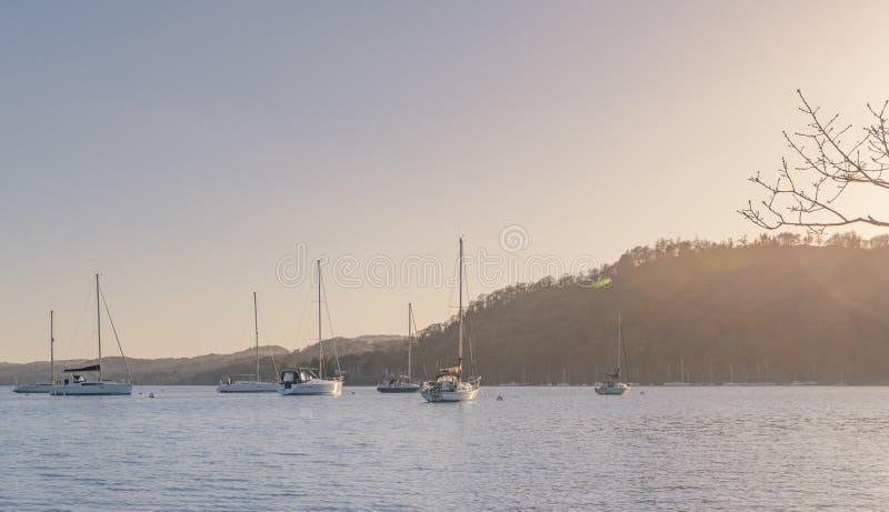 Barcos de navegación en el lago Windermere, distrito del lago - primavera puesta del sol marzo de 2019 temprano imágenes de archivo libres de regalías