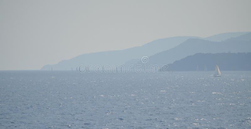 Barcos de navegación en la niebla de sombras azules de las costas de Elba Island fotografía de archivo libre de regalías