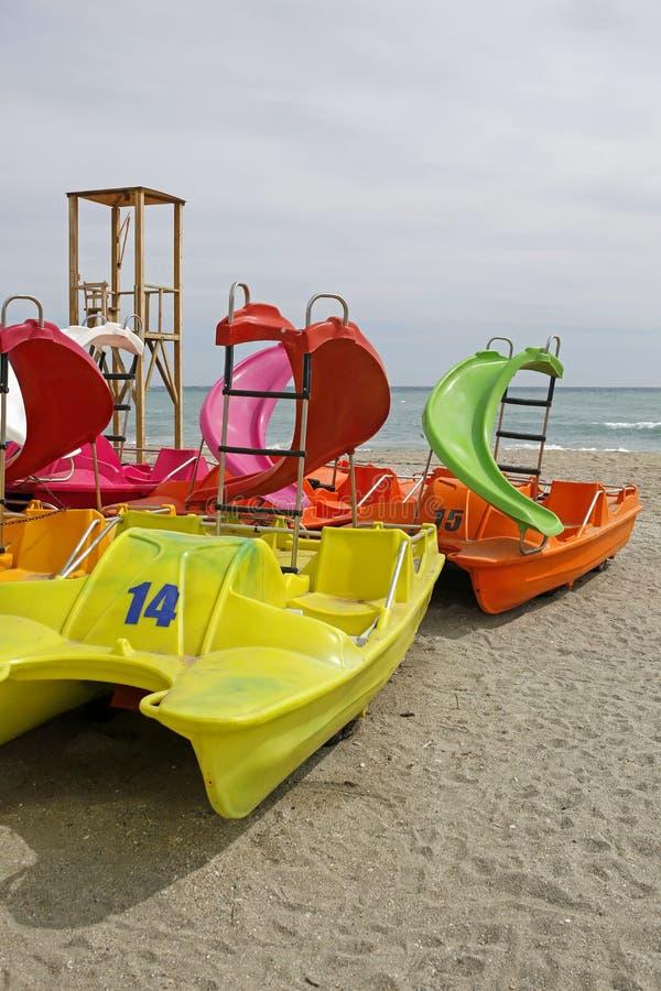 Barcos de pá coloridos do pedalo na praia foto de stock