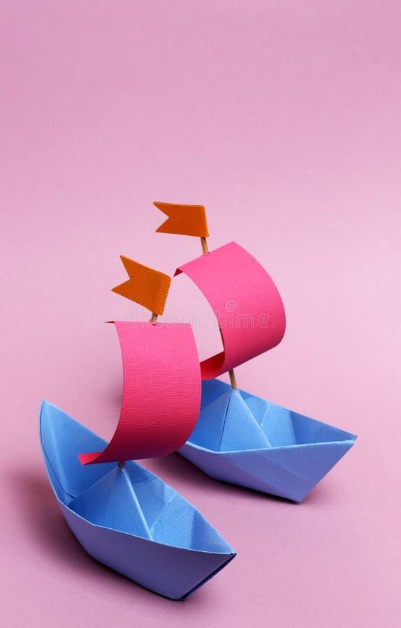 2 barcos de papel em um fundo cor-de-rosa fotos de stock