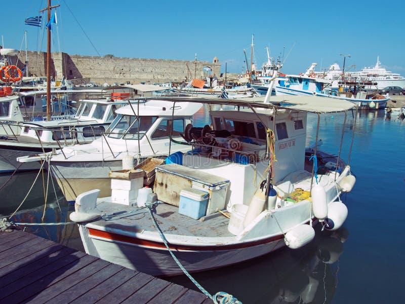 Barcos de pesca amarrados no porto da cidade de Rodes com as paredes históricas da cidade imagem de stock