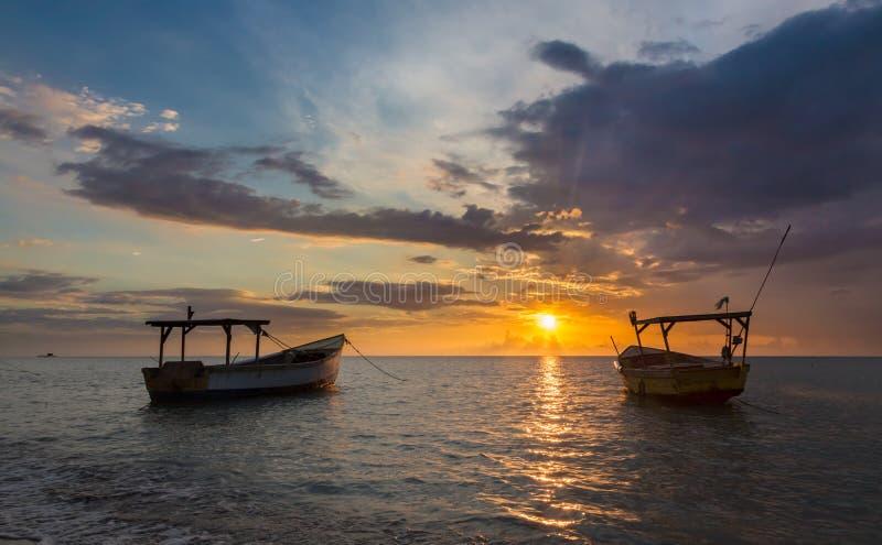 Barcos de pesca e por do sol dourado sobre o mar imagem de stock