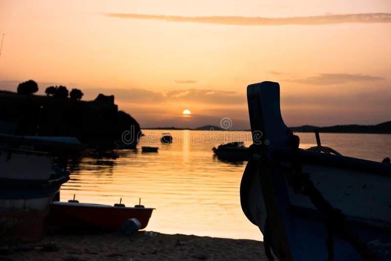 Barcos de pesca em uma praia na frente das ruínas de uma fortaleza romana no por do sol, Sithonia fotos de stock royalty free