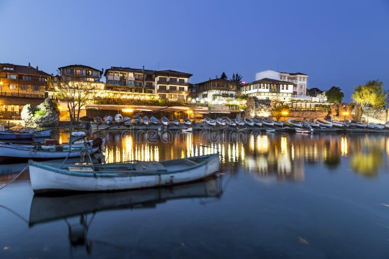 Barcos de pesca en ciudad costal en la noche foto de archivo