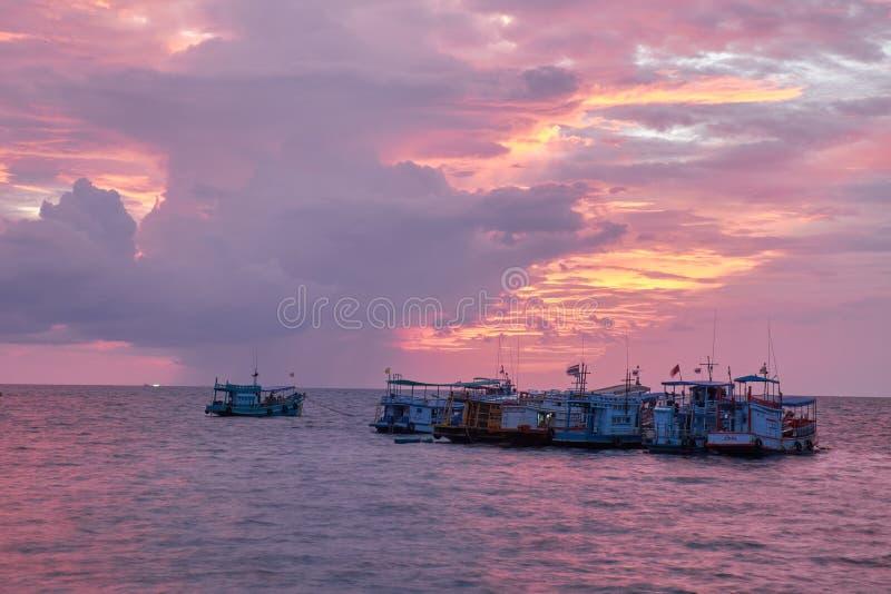 Barcos de pesca en el mar bajo puesta del sol roja y anaranjada imagen de archivo libre de regalías