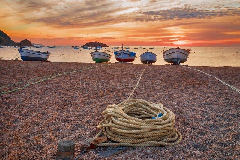 Barcos de pesca en la costa mediterránea en el fondo de la salida del sol foto de archivo