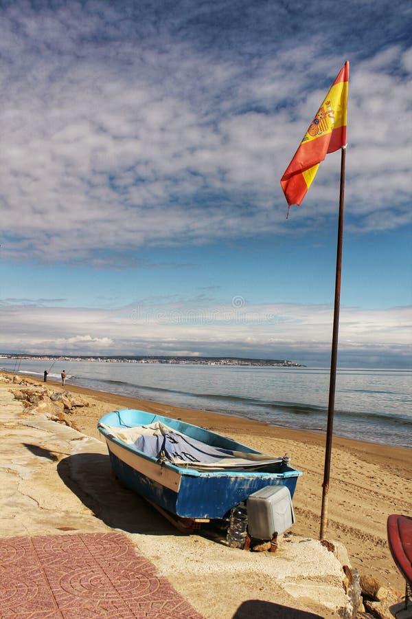 Barcos de pesca en la orilla debajo de la bandera española por la mañana foto de archivo
