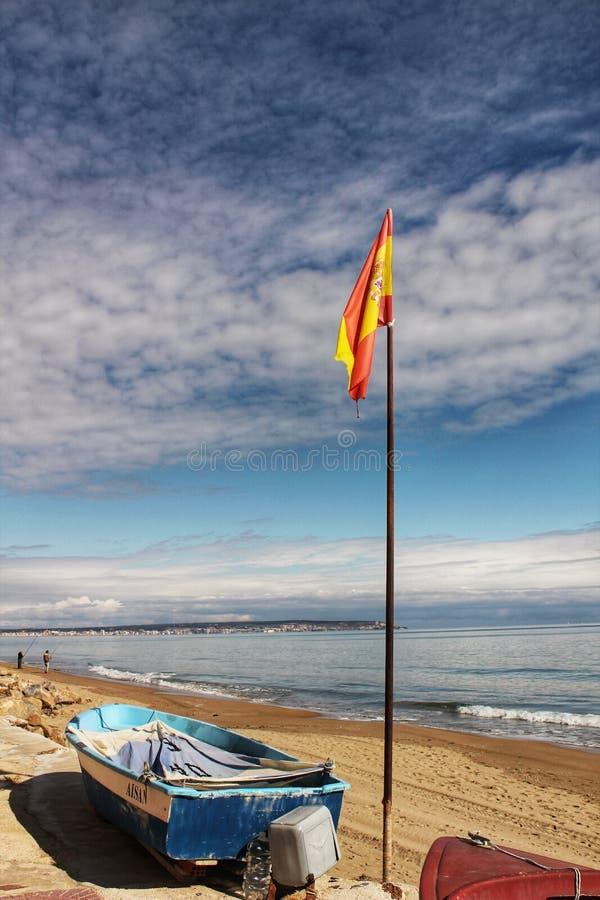 Barcos de pesca en la orilla debajo de la bandera española por la mañana fotografía de archivo