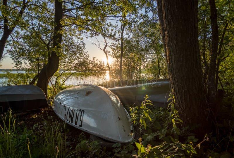 Barcos de pesca en la orilla del lago Svir en la salida del sol fotografía de archivo