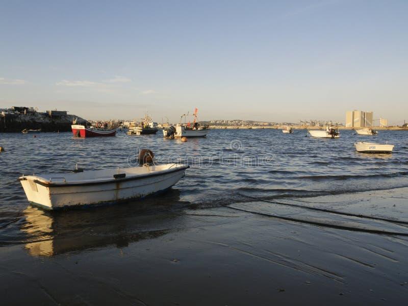 Barcos de pesca de flutuação entrados em uma costa imagens de stock