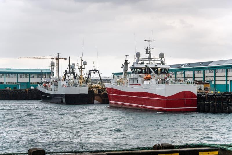 Barcos de pesca grandes en puerto en un día lluvioso fotos de archivo
