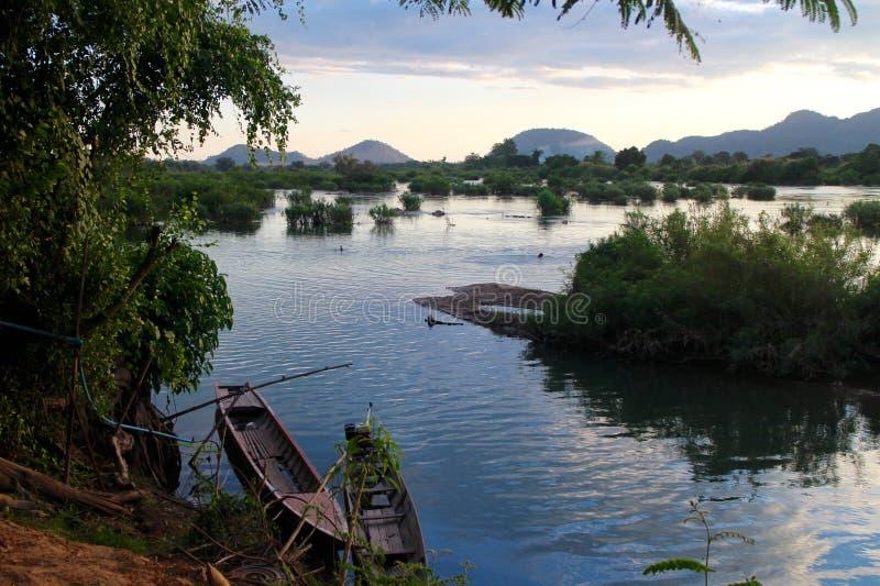 Barcos de pesca no Mekong River no por do sol com os montes no fundo fotografia de stock