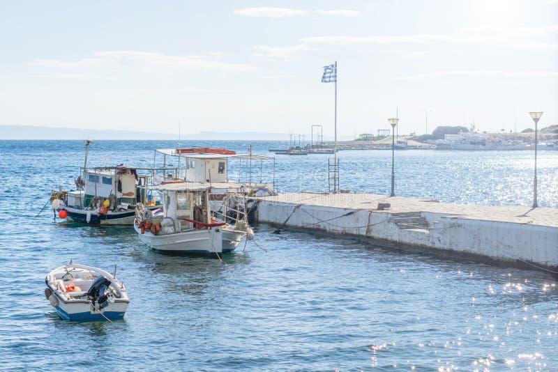 Barcos de pesca sobrecarregados brancos pequenos ancorados ao lado da doca imagem de stock